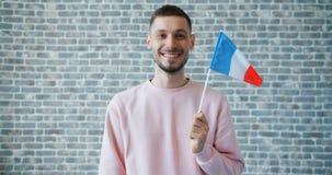 Portret szczęśliwy młody człowiek z Francuską flagą państowową na ściany z cegieł tle zdjęcie wideo