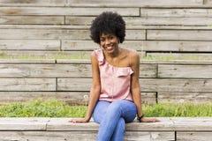 Portret Szczęśliwy młody piękny afro amerykański kobiety obsiadanie Zdjęcia Stock