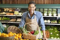 Portret szczęśliwy młody sprzedawca z jarzynowym koszem w supermarkecie Zdjęcia Royalty Free