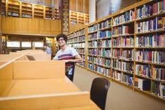 Portret szczęśliwy młody uczeń używa jego laptop w bibliotece obraz stock