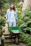 Portret szczęśliwy ogrodniczki dosunięcia wheelbarrow przy ogródem Fotografia Royalty Free