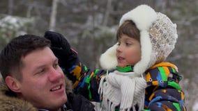 Portret szczęśliwy ojciec i bardzo śliczna szczęśliwa chłopiec, jego syn w śnieżnym zima parku chłopak się uśmiecha atrakcyjna ro zbiory wideo