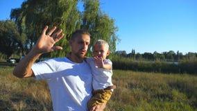 Portret szczęśliwy ojciec i mały syn macha ich ręki w kamerę przy parkiem Młody tata trzyma jego dziecka w rękach przy zbiory