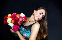 Portret Szczęśliwy, piękny kobiety obsiadanie z bukietem róże, na czarnym tle Prezent dla kobiety fotografia royalty free