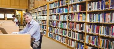 Portret szczęśliwy profesora obsiadanie przy biurkiem używać jego laptop fotografia royalty free