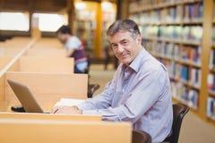 Portret szczęśliwy profesora obsiadanie przy biurkiem używać jego laptop obrazy stock