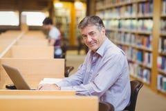 Portret szczęśliwy profesora obsiadanie przy biurkiem używać jego laptop zdjęcia stock