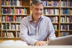 Portret szczęśliwy profesora obsiadanie przy biurkiem używać laptop zdjęcie royalty free