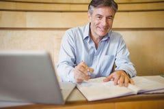 Portret szczęśliwy profesora writing w książce przy biurkiem obraz stock