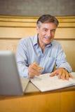 Portret szczęśliwy profesora writing w książce przy biurkiem obraz royalty free