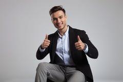 Portret szczęśliwy przypadkowy mężczyzna robi ok znakowi podczas gdy siedzący fotografia stock