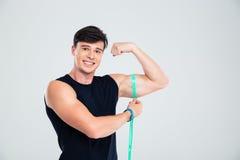 Portret szczęśliwy sprawność fizyczna mężczyzna mierzy jego bicepsy Fotografia Stock