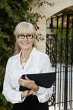 Portret szczęśliwy starszy żeński agent z schowkiem Obrazy Royalty Free