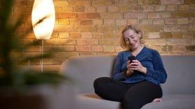 Portret szczęśliwy starszy caucasian damy obsiadanie na kanapie i dopatrywanie w smartphone w wygodnej domowej atmosferze obraz royalty free