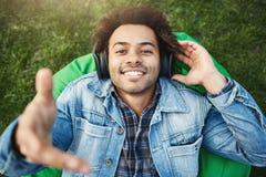 portret szczęśliwy szczery uśmiechnięty afroamerykański studencki lying on the beach na bobowej torby krześle i rozciąganie ręce  fotografia stock