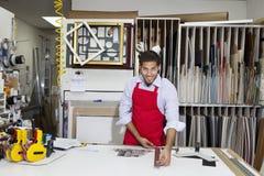 Portret szczęśliwy wykwalifikowany robotnik mierzy z metrowym kijem w warsztacie Obrazy Royalty Free