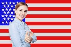 Portret szcz??liwa ameryka?ska dziewczyna z kciukiem przeciw w g?r? usa flagi t?a Podr??uje j?zyka angielskiego poj?cie i uczy si obraz royalty free