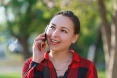Portret szcz??liwa m?oda brunetki dziewczyna z smartphone w jej r?ce, nastroszony jej ucho Dziewczyna opowiada na mobilnym i u?mi zdjęcie stock