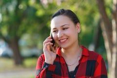 Portret szcz??liwa m?oda brunetki dziewczyna z smartphone w jej r?ce, nastroszony jej ucho Dziewczyna opowiada na mobilnym i u?mi obraz royalty free