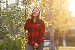 Portret szcz??liwa m?oda brunetki dziewczyna z smartphone w jej r?ce, nastroszony jej ucho Dziewczyna opowiada na mobilnym i u?mi obraz stock