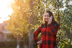 Portret szcz??liwa m?oda brunetki dziewczyna z smartphone w jej r?ce, nastroszony jej ucho Dziewczyna opowiada na mobilnym i u?mi fotografia stock