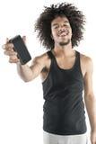 Portret szczęśliwy młody człowiek pokazuje telefon komórkowego nad białym tłem Fotografia Royalty Free
