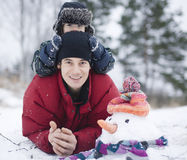 Portret szczęśliwy ojciec z jego synem outside z bałwanem Fotografia Royalty Free