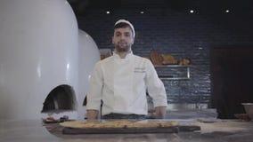 Portret szef kuchni w bielu jednolitym demonstrujący świeżo piec fatayer lying on the beach na drewnianej desce cutted na kawałka zbiory wideo