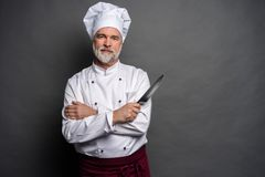 Portret szefa kuchni kucharza mienia dojrzali knifes odizolowywający na czarnym tle obrazy royalty free