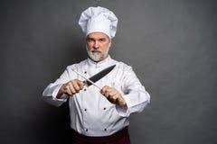 Portret szefa kuchni kucharza mienia dojrzali knifes odizolowywaj?cy na czarnym tle obraz royalty free