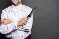 Portret szefa kuchni kucharza mienia dojrzali knifes odizolowywaj?cy na czarnym tle obraz stock