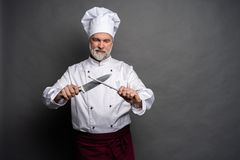 Portret szefa kuchni kucharza mienia dojrzali knifes odizolowywaj?cy na czarnym tle zdjęcia stock