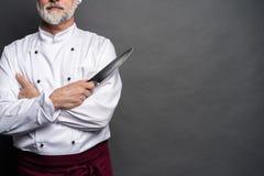 Portret szefa kuchni kucharza mienia dojrzali knifes odizolowywaj?cy na czarnym tle zdjęcie stock