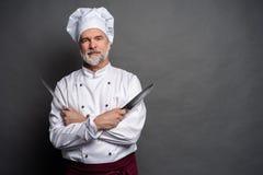 Portret szefa kuchni kucharza mienia dojrzali knifes odizolowywaj?cy na czarnym tle obrazy stock