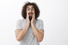 Portret szokujący przytłaczający śmieszny Wschodni facet z afro fryzurą, dyszący, być bezmowny od niespodzianki, trzyma Obrazy Stock
