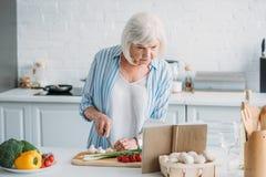 portret szuka przepis w cookery książce przy kontuarem starsza dama podczas gdy kulinarny gość restauracji zdjęcia royalty free