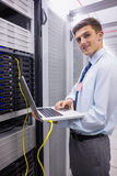 Portret technik używa laptop podczas gdy analizujący serweru Zdjęcia Royalty Free