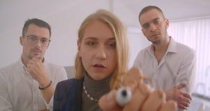 Portret trzy collleagues pracuje wpólnie w biurze indoors Bizneswoman pisze pomysłach na ekranie podczas gdy zdjęcie wideo