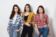 Portret trzy młodej pięknej nikłej dziewczyny kobiety w szkockich krat koszula czerwień, kolor żółty i błękit na białym tle, fotografia royalty free