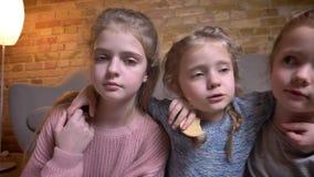 Portret trzy małej caucasian dziewczyny ściska each inny i spada na podłodze w cosy domowej atmosferze zbiory wideo