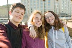 Portret trzy przyjaci?? nastoletnia ch?opiec i dwa dziewczyny u?miecha si? selfie outdoors i bierze fotografia royalty free