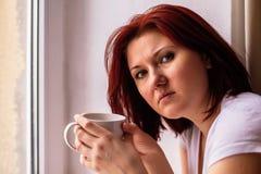 Portret trzyma białego kubek kawowy pobliski okno i patrzeje kamerę kobieta Kobieta stresował się i nieszczęśliwa twarz kosmos ko zdjęcie royalty free