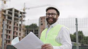 Portret trzyma budowa rysunki w jego ręce pomyślni potomstwa inżynier lub architekt jest ubranym białego hełm, zdjęcie wideo