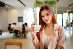 Portret trzyma filiżankę kawy w jej ręce na plamy tła sklep z kawą piękna kobieta Obrazy Royalty Free