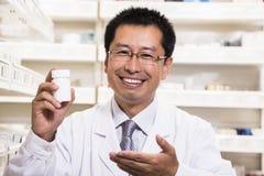 Portret trzyma recepturową lekarstwo butelkę w jego ręce uśmiechnięta farmaceuta obraz stock