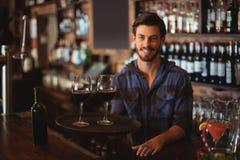 Portret trzyma tacę z szkłami czerwone wino bar oferta zdjęcia stock