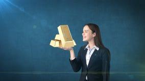 Portret trzyma złotych bary na otwartej ręki palmie nad odosobnionym pracownianym tłem młoda kobieta, pojęcia prowadzenia domu po Fotografia Royalty Free