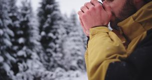 Portret turysta w żółtej kurtce w ciężkim zima dniu po środku śnieżnego lasu marznącego bierze żelazną filiżankę zbiory