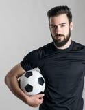 Portret twardy ufny gracz piłki nożnej jest ubranym czarną dżersejową koszulki mienia piłkę pod jego ręką obrazy royalty free