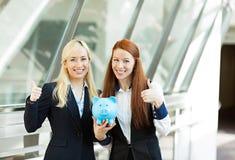 Portret twee gelukkige bedrijfsvrouwen die spaarvarken houden die thum geven stock afbeeldingen